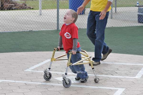 Young boy with a physical disability walks across the baseball field with is walker