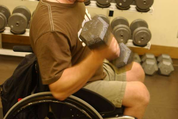 Young man in wheelchair lifts weights at the gym