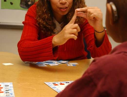Teacher works with hearing imapaired student, by communicating through sign language