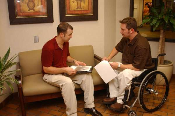 Man with a physical disability speaks with a co-worker