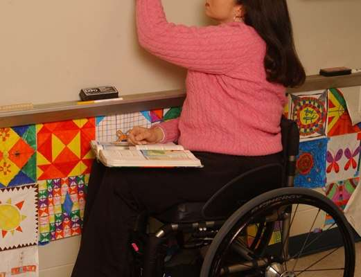 Teacher using a wheelchair writes on the blackboard for her students