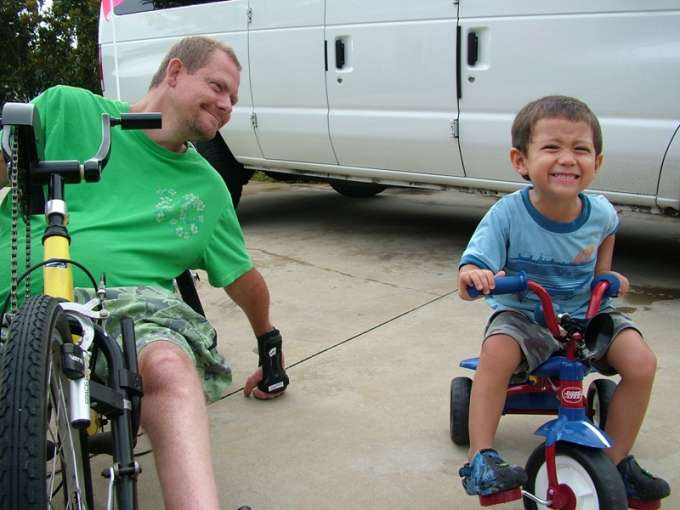 Father in a handcycle lovingly looks at his young son in his tricycle
