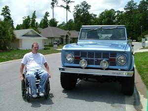 Man in a wheelchair poses next to his vintage truck