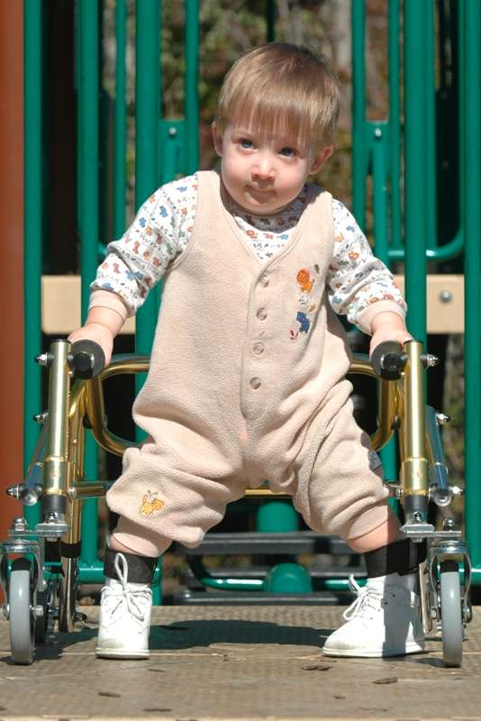 Very young boy with a walker plays in the playground
