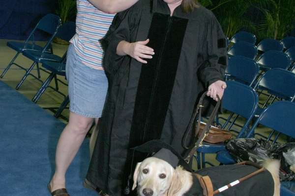 Young woman with her service animal preparing to gradute college, the dog is clad in a cap and gown just like his owner!