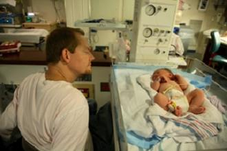 Father looks at his newborn baby at the hospital