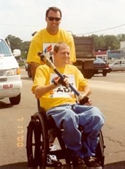 Man in a wheelchair holding the torch during an ADA marathon