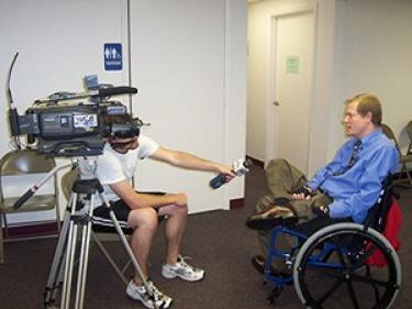 Behind the scenes shot of a man in a wheelchair giving an interview