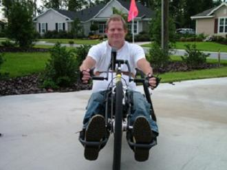 Man poses while using his handcycle