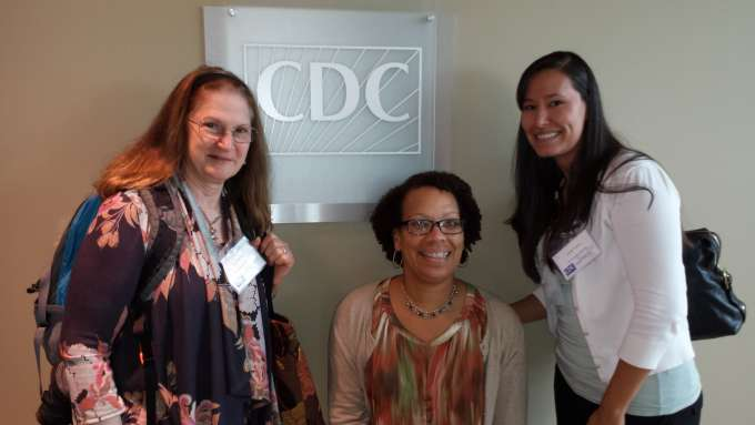 Three of our DHP staff pose in front of a CDC sign