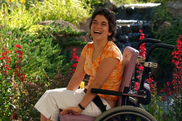 woman with a developmental disability in a wheelchair smiles for the camera